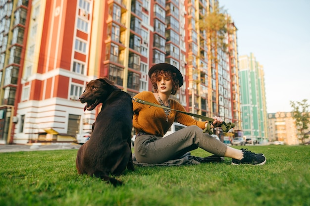 Девушка сидит во дворе на лужайке с собакой на поводке