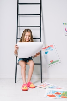 Girl sitting on ladder with drawings