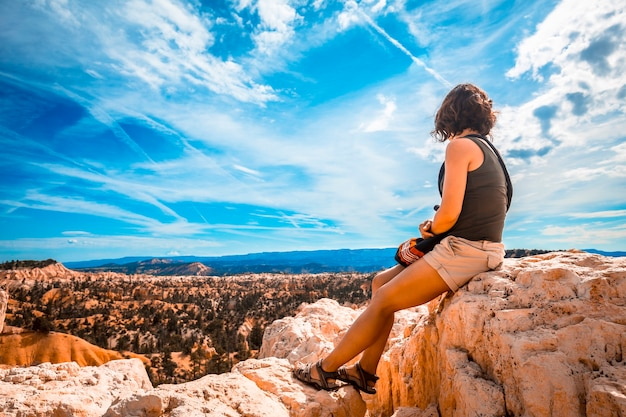 A girl sitting looking at the views from the sunrise point in bryce national park. utah, united states