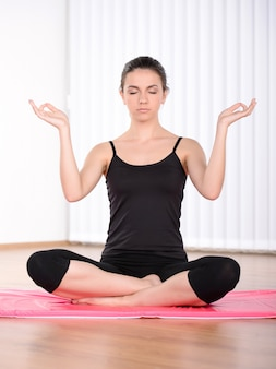 Girl sitting in the lotus position on the rug