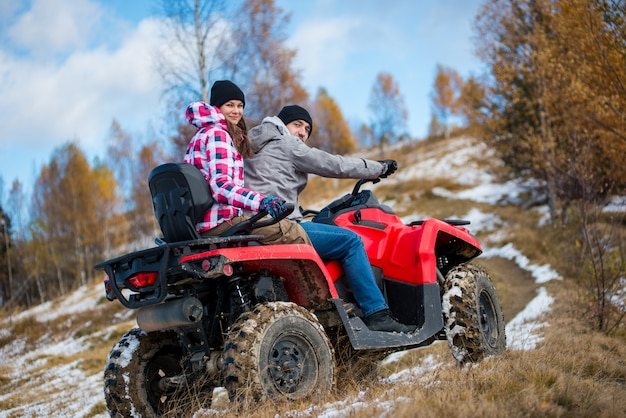 Girl sitting behind man hugging him on red four-wheeler atv and looking to the camera at snowy hill in the mountains