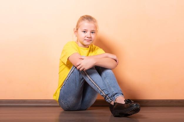 Девушка сидит обиделась на полу, светло-оранжевом фоне. для любых целей.