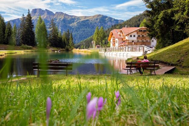 山の景色を望む湖のそばのベンチに座っている女の子。イタリアのドロミティ。イタリア