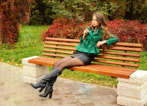 Девушка сидит на скамейке в парке.