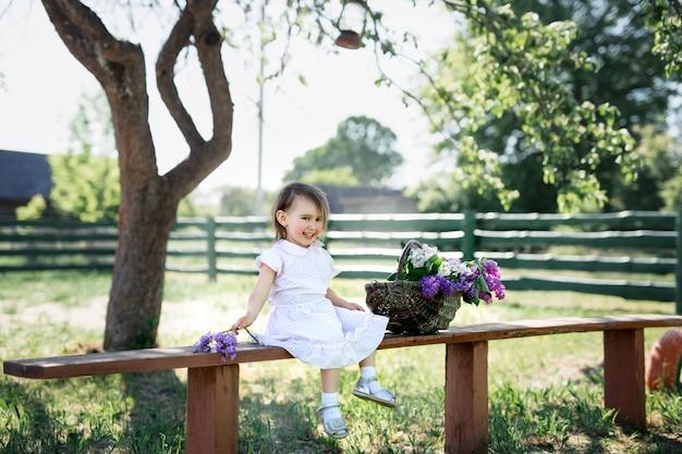 ライラックのバスケットと村のベンチに座っている女の子