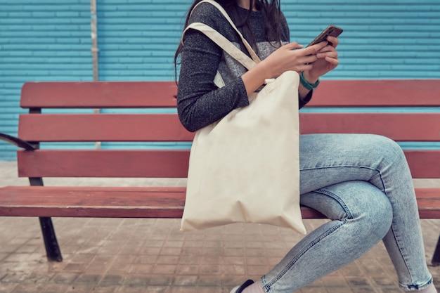 모바일을 사용하는 동안 어깨에 가방을 메고 벤치에 앉아 있는 소녀