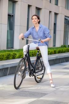 Девушка сидит на велосипеде на улице