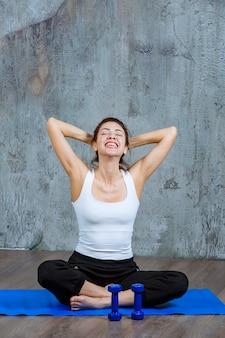 蓮華座で青いヨガマットの上に座って瞑想している女の子。