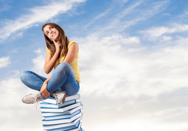 Девушка сидит на книгах