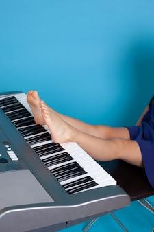 의자에 앉아 그녀의 발로 피아노를 연주하는 소녀