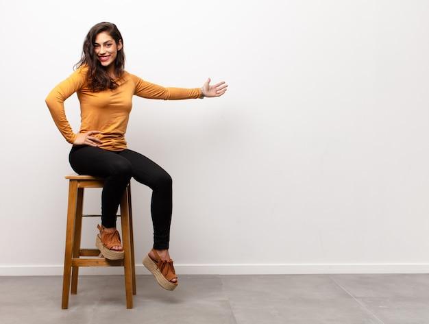 手で何かを見せながら椅子に座っている女の子