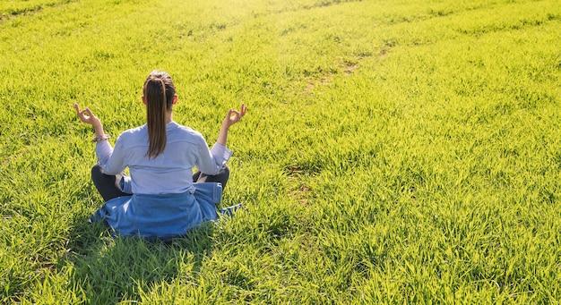 Девушка сидит на зеленом лугу весной с позой для медитации в очень солнечный день