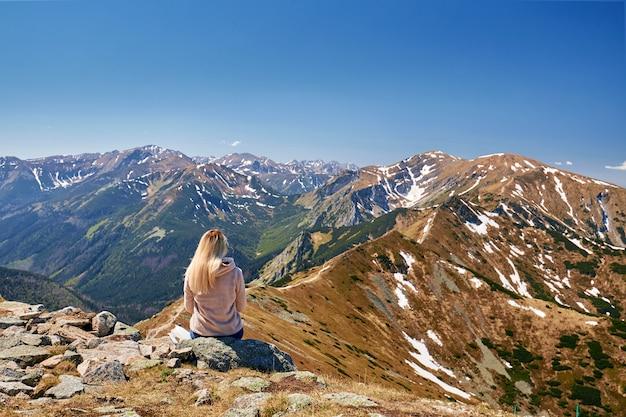 Девушка сидит на горе спиной и смотрит на горы