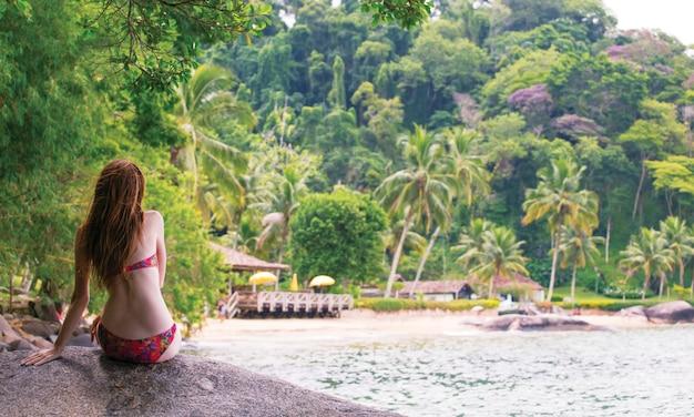 Девушка сидит на камне и смотрит на небольшой бразильский пляж
