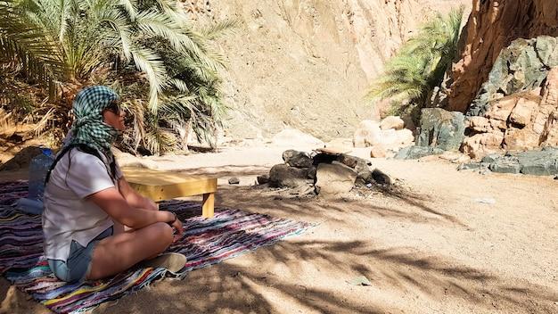 ヨガの蓮華座でアラビア絨毯に座っている女の子。エジプトの峡谷を巡る遠足の暑い晴れた日にヤシの木の木陰に隠れて、砂漠で休んでいる若い女性の観光客。