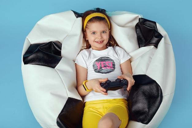 Девушка сидит на стуле с фасолью, держит джойстик и играет в видеоигры