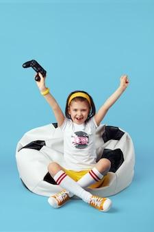 Девушка сидит на кресле-мешке с фасолью, поднимая руки вверх, празднуя победу