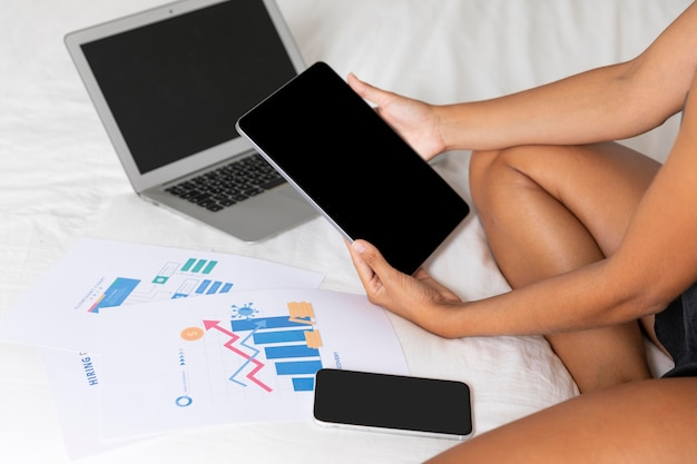 Девушка сидит на кровати с ноутбуком и планшетом