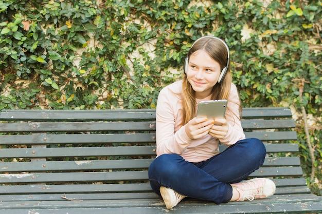 ヘッドフォンで携帯電話で音楽を聴くベンチに座っている女の子