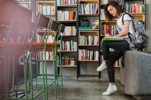 Девушка, сидя на стуле, писать на ноутбуке