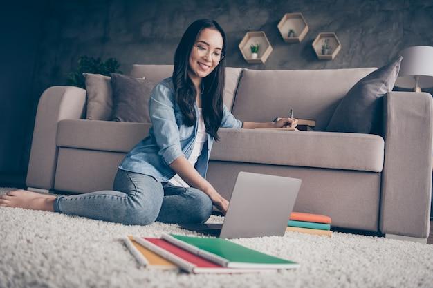 Девушка сидит на полу и работает на ноутбуке