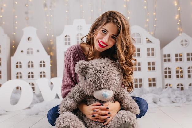 Девушка сидит на полу с ярким макияжем, мило улыбается и обнимает серого плюшевого мишку