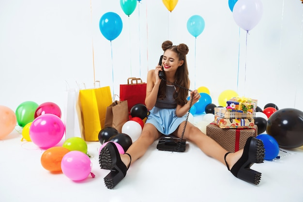 Девушка сидит на полу с домашним телефоном, получая поздравления с днем рождения