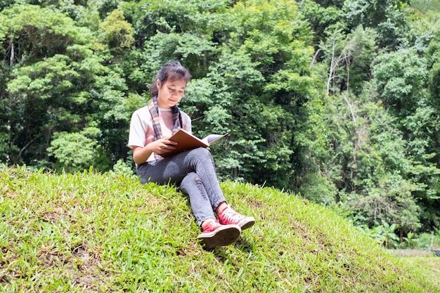 公園の緑の草に座って本を読んでいる少女。