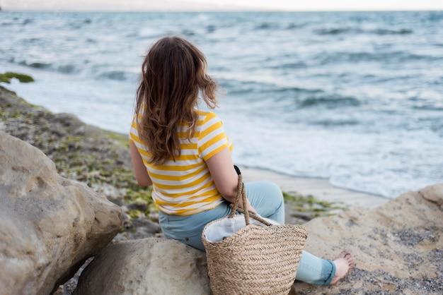 海に面した岩の上に座っている女の子