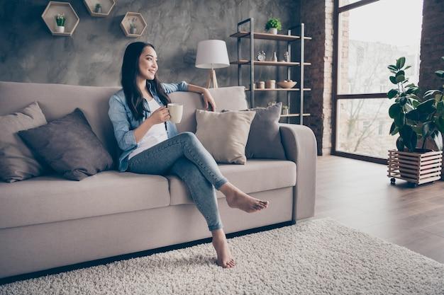 Девушка сидит на диване и пьет кофе