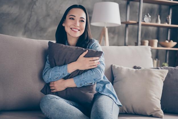 Девушка сидит на диване и обнимает подушку