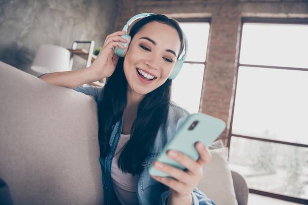 소녀는 소파에 앉아 음악을 듣고 전화를보고