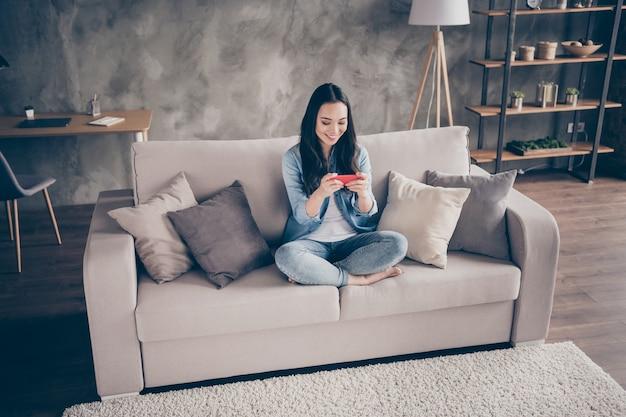 Девушка сидит на диване, глядя на телефон