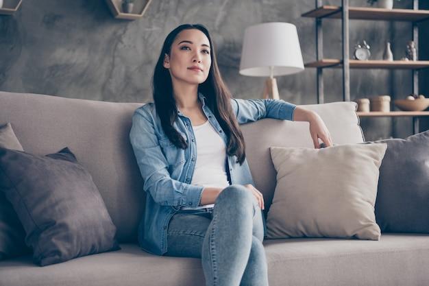 Девушка сидит на диване и смотрит телевизор