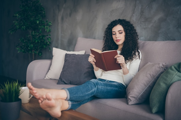 Девушка сидит на диване и читает книгу с длинными скрещенными ногами в современном лофте в индустриальном стиле в интерьере гостиной в помещении