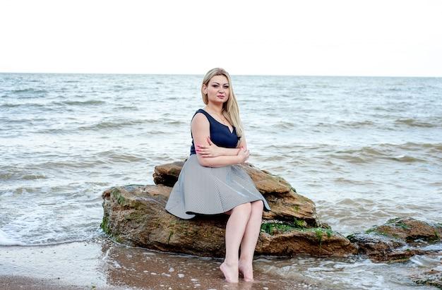 Девушка сидит на пляже в пасмурную погоду, в платье