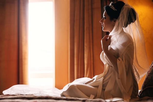 窓の前のベッドに座っている女の子。結婚式のベールと白いローブの花嫁のプロファイル。
