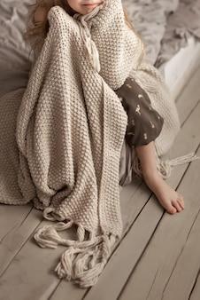 空白に包まれた寝室のベッドに座っている女の子