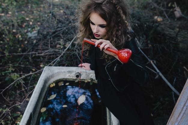 Девушка сидит на краю ванны с красным зельем