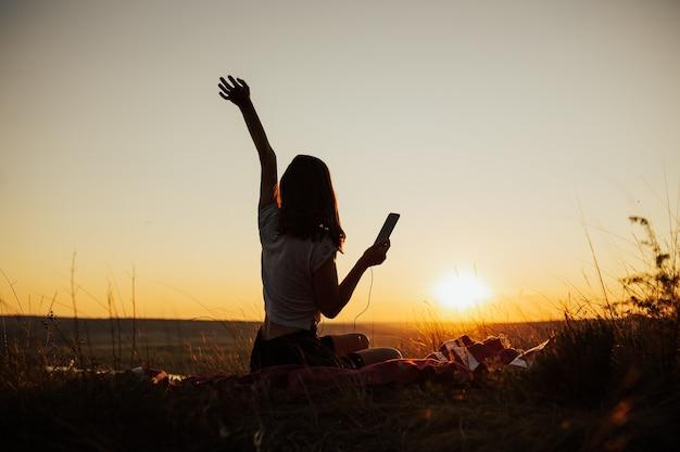 ゴージャスな夕日のフィールドに座って、夕日のイヤホンで携帯電話アプリを使用して音楽を聴いて楽しんでいる女の子。