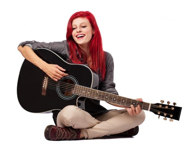 여자는 바닥에 앉아서 그녀의 기타 연주