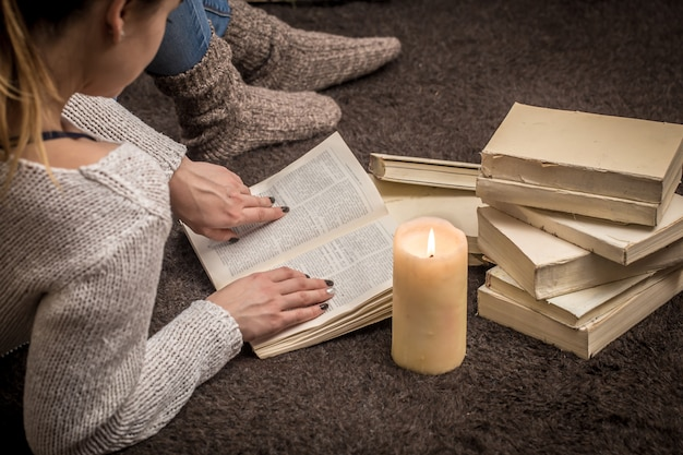 Девушка сидит на полу в окружении множества белых книг и большой свечи