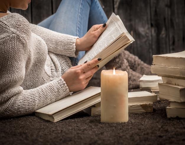 多くの白い本と大きなキャンドルに囲まれた床に座っている女の子