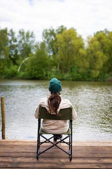 Девушка сидит на пирсе, ловит рыбу на озере, улыбается, вид сзади. активный отдых на свежем воздухе, прекрасный летний день.