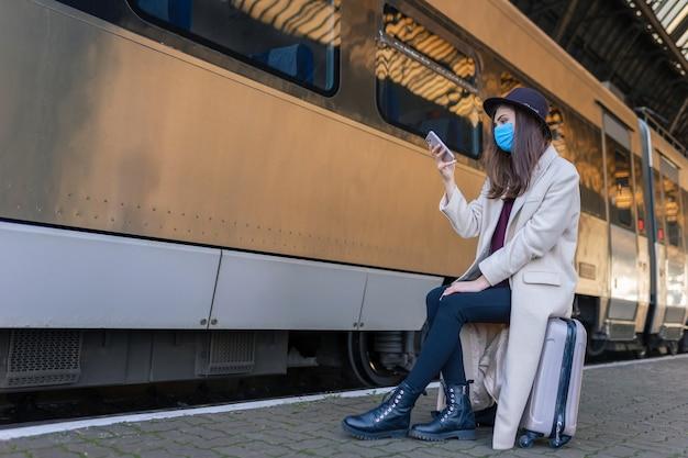 プラットフォームに座ってスマートフォンを使用している女の子