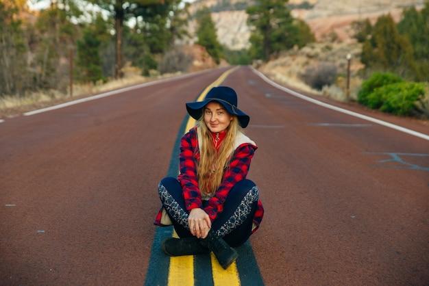 スプリングデールの町の近くのユタ州南西部のザイオン国立公園の道路に座っている女の子