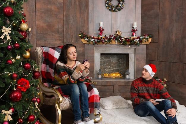 ロッキングチェアに座って携帯電話でインターネットを提供している女の子、装飾された暖炉とプレゼントのあるクリスマスツリーのある部屋の敷物の上に座っているボーイフレンド