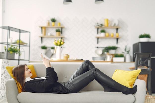 Девушка сидит на диване и пользуется телефоном