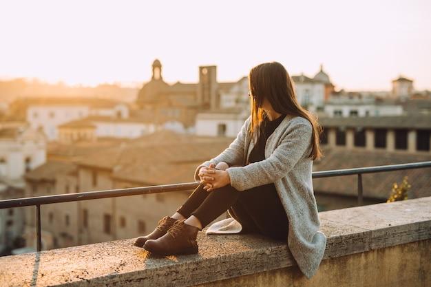 美しい夕日と街を見下ろす建物の上に座っている女の子