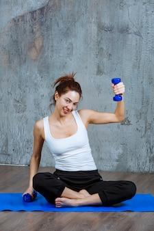 ヨガマットの上に座って、ダンベルで片腕のトレーニングをしている女の子。
